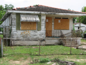 Run down single family house behind a chain link fence