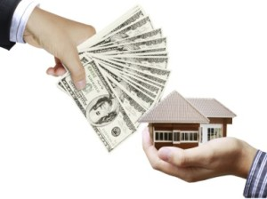 A hand with multiple hundred dollar bills stretching out to a hand that is holding a house